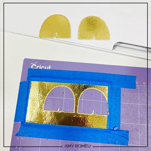 cut rainbow earring shapes on Cricut purple mat