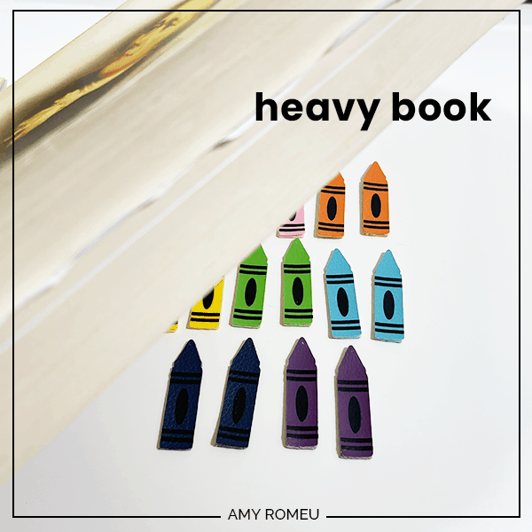 pressing glued crayon earrings under a book