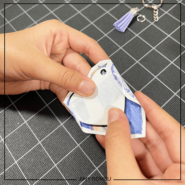 placing heat resistant tape on sublimation keychain blank