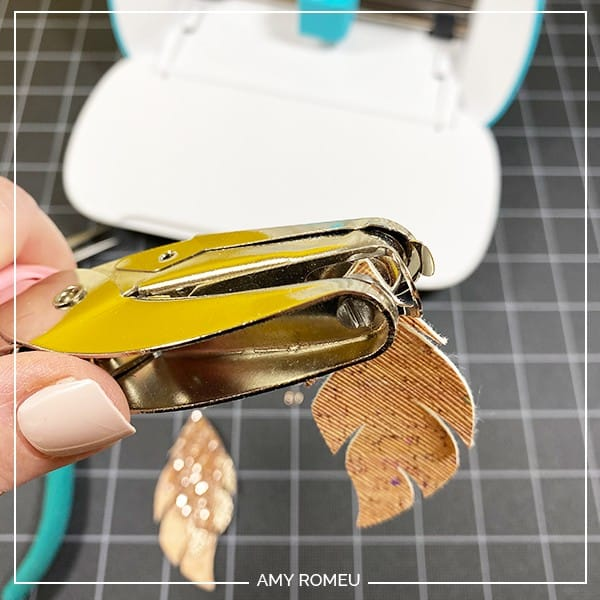 punching earring holes in faux leather earring shapes cut with a Cricut Joy