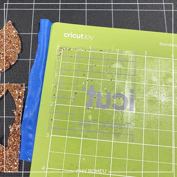 glitter faux leather residue stuck to transfer tape on a Cricut Joy cutting mat
