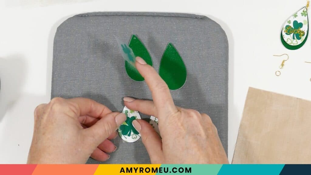 preparing to press heat transfer vinyl on St. Patrick's Day faux leather earrings
