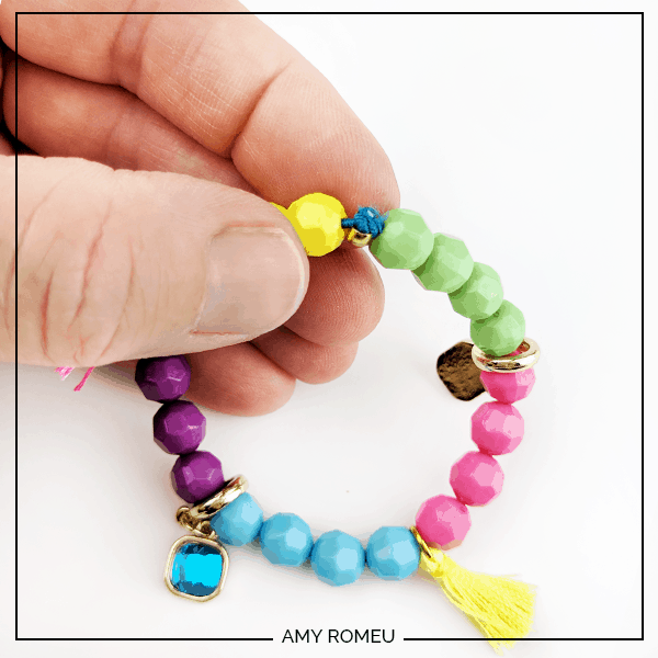 knotted cord while making a stretchy stack bracelet with beads, charms and tassels