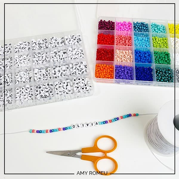 letter beads, seed beads, scissors, cord