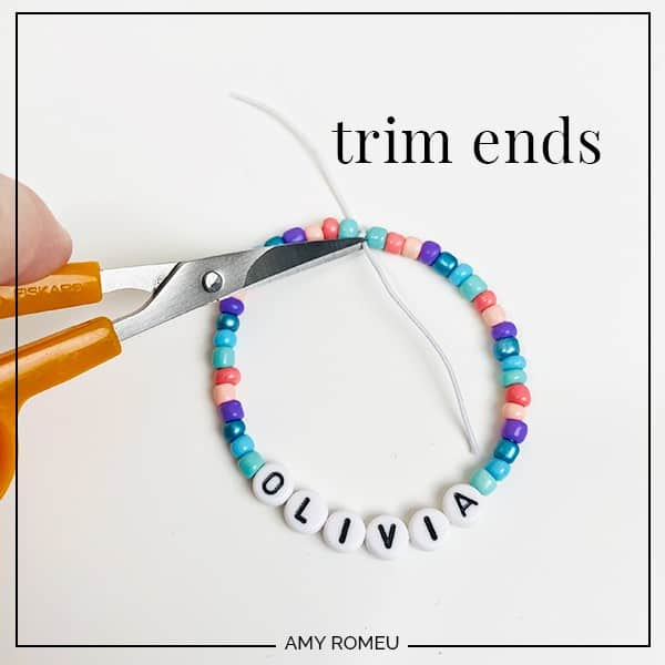 trimming ends of stretchy bracelet with scissors